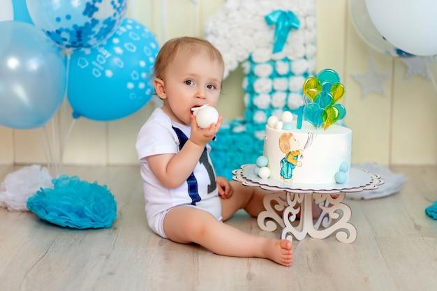 Neonato che mangia la sua torta con le mani, bambino di 1 anno, infanzia felice, compleanno dei bambini
