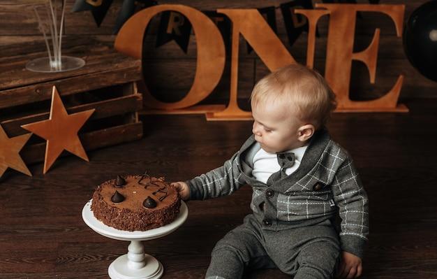 Un bambino in abito grigio festeggia il suo compleanno su uno sfondo marrone