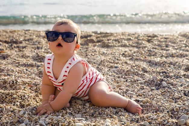 Neonato in cappello sulla spiaggia di ciottoli gioca
