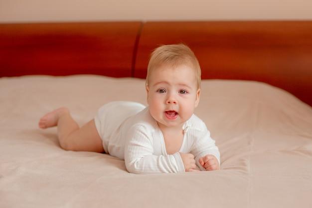 Il neonato giace a pancia in giù sul letto in camera da letto