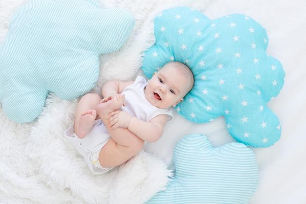 Bambino sdraiato a letto prima di andare a letto, carino, ridente, bambino di sei mesi e sorridente