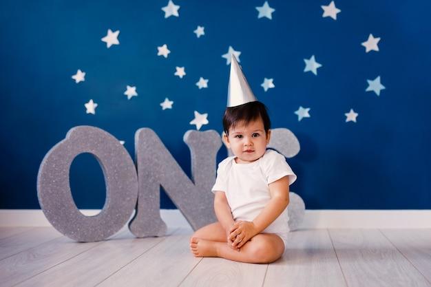 Neonato di un anno che indossa un corpo bianco e un cappello di carta festivo siede sul pavimento su uno sfondo blu con stelle e grandi lettere d'argento uno.