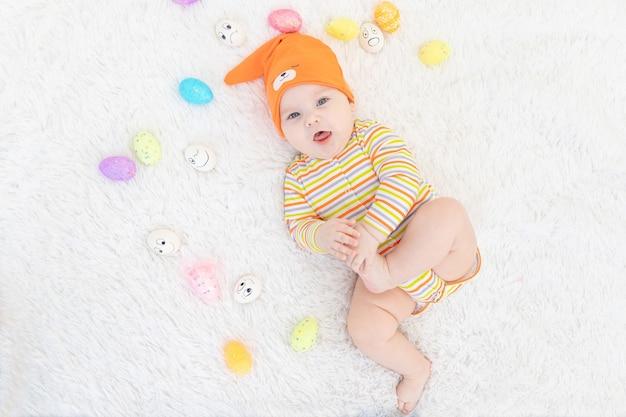 Neonato in vestiti arancioni che si trovano con le uova di pasqua, piccolo bambino sorridente divertente sveglio.