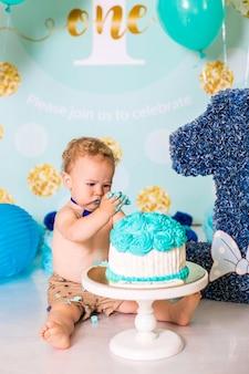 Neonato che gioca con una torta durante la festa di compleanno di smash torta