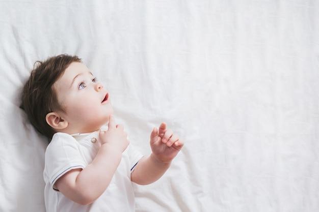 Ritratto del neonato con l'espressione divertente del fronte scioccato e la reazione curiosa sul fondo bianco del letto