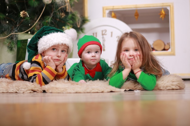 Neonato in costume da elfo rosso verde con suo fratello maggiore e sorella in cappelli di babbo natale seduto sotto l'albero di natale con scatole regalo.