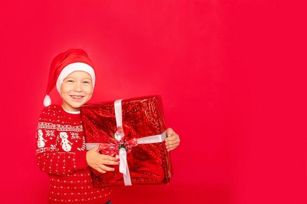 Neonato su uno sfondo rosso isolato con un regalo in un cappello da babbo natale