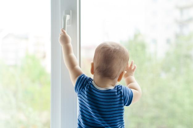 Il bambino si siede sul davanzale e cerca di aprire la finestra tirando la maniglia