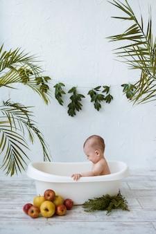 Il neonato si siede in una vasca bianca con le mele su una superficie bianca con le piante