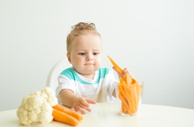 Bambino seduto su una sedia childs mangiare fette di carota su sfondo bianco.