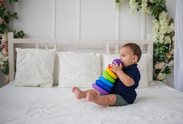 Neonato che si siede lateralmente sul letto e gioca con un giocattolo piramidale