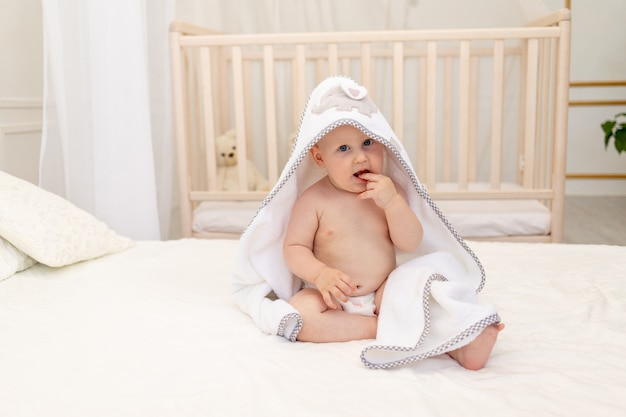 Neonato che si siede su un letto bianco in un asciugamano bianco
