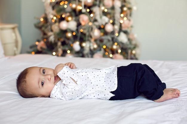 Neonato di sei mesi sdraiato sul letto in una camicia bianca accanto all'albero di natale