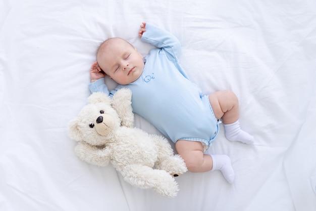 Il neonato dorme sul letto sdraiato sulla schiena con un orso di peluche in pigiama blu