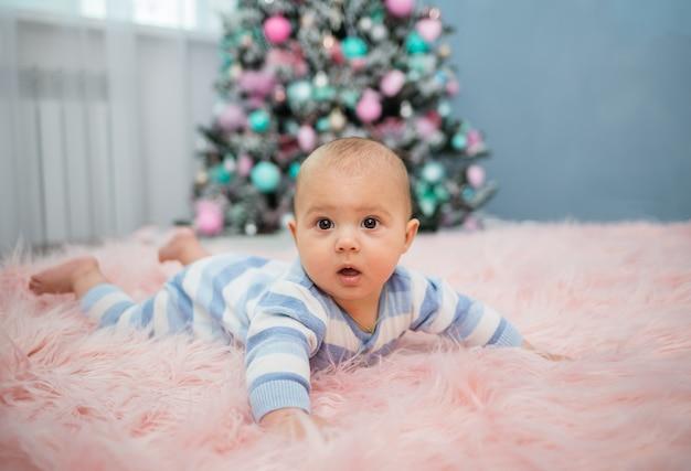 Un bambino in una tuta a righe giace su una coperta di pelliccia rosa e guarda la telecamera sullo sfondo di un albero di natale