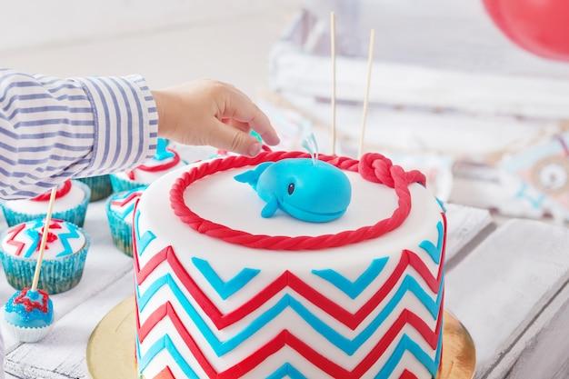 Neonato che tocca la torta di compleanno con le sue dita