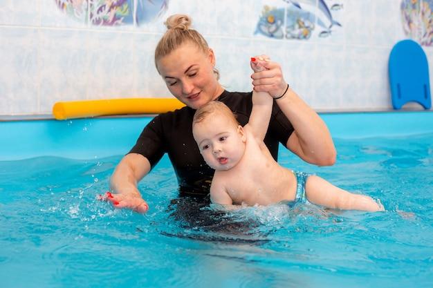 Il neonato si allena per nuotare in piscina con un allenatore