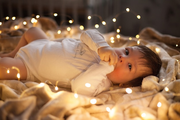 Il neonato in un body bianco giace su una coperta con ghirlande di luci a natale.