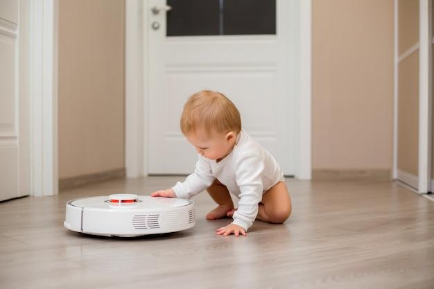 Bambino in abiti bianchi con un aspirapolvere robot sul pavimento della casa