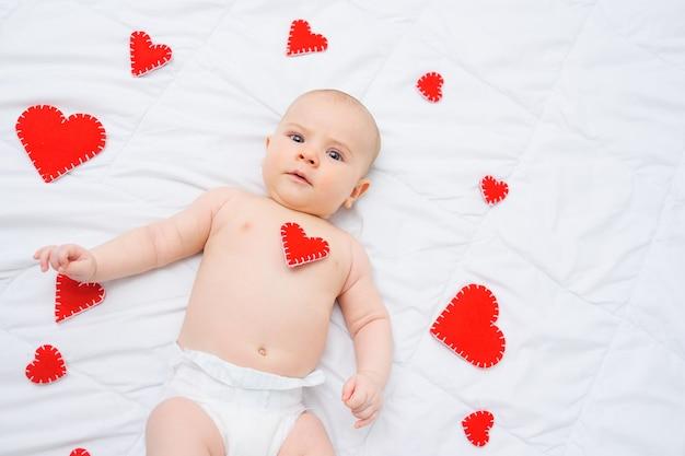 Il neonato in un pannolino bianco si trova contro il giorno di biglietti di s. valentino di amore dei cuori rossi