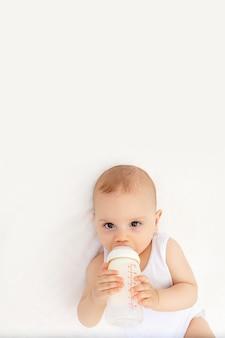 Neonato con una bottiglia di latte su un letto bianco a casa