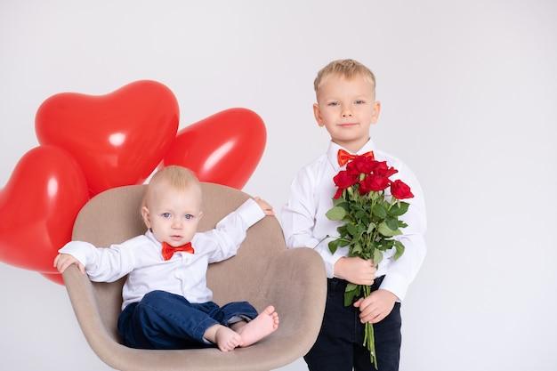 Neonato con palloncini cuore si siede in sedia e fratello ragazzo con bouquet di rose sul muro bianco.