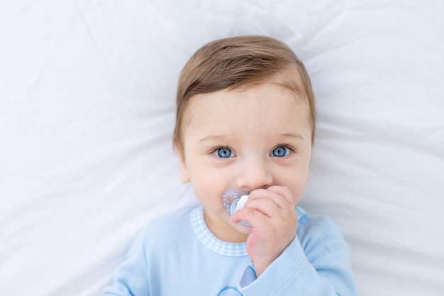 Neonato con il ciuccio sul letto prima di andare a letto in tuta blu, piccolo bambino sano e felice