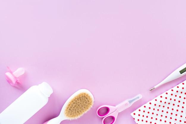 Kit per la cura del bambino su sfondo rosa, vista dall'alto, copyspace. concetto di igiene dei bambini. composizione piatta con accessori per bambini, sfondo..