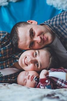 Bambino in una camicia a scacchi con papà e mamma. bambino e i suoi genitori. foto di famiglia. appoggiarsi l'un l'altro sulle guance