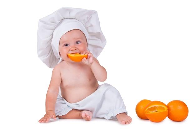Bambino in abiti da chef sta mangiando arancia
