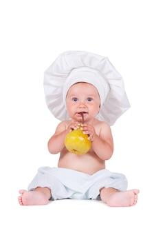 Bambino in abiti da chef sta mangiando pera