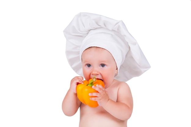 Bambino in abiti da chef sta mangiando pepe