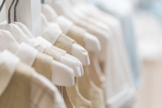 Accumulazione dei vestiti del bambino che appende nella stanza di manifestazione Foto Premium