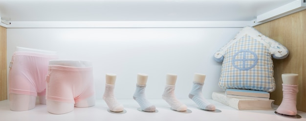 Vestiti del bambino che appendono sulla corda da bucato, su sfondo luminoso Foto Premium