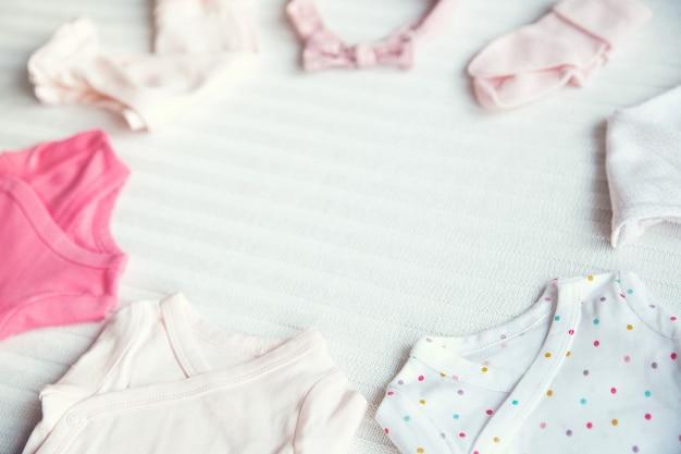 Vestiti per bambini su sfondo di tessuto pastello chiaro delicato umore morbido e accogliente