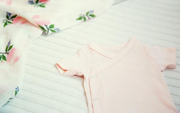 Vestiti per bambini e necessità su sfondo di tessuto leggero delicato umore morbido e accogliente