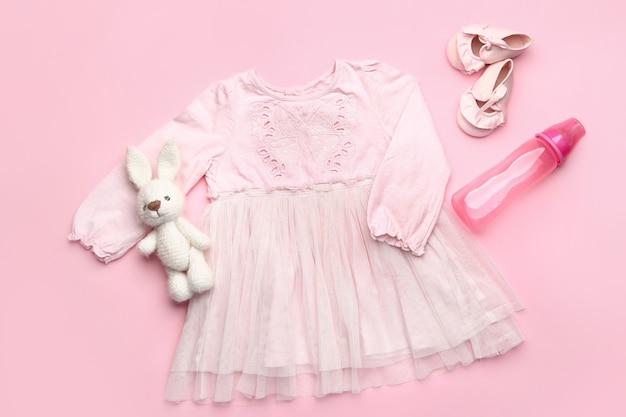 Vestiti del bambino con giocattolo, stivaletti e bottiglia sul colore
