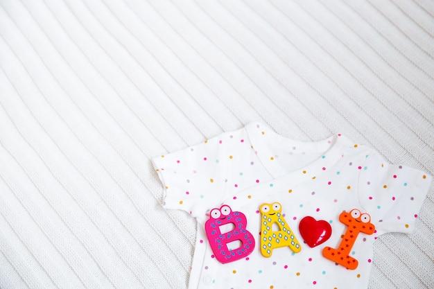 Vestiti del bambino con lettere giocattolo su sfondo di tessuto bianco.