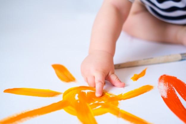 Il bambino gattona sul pavimento giocando con le vernici