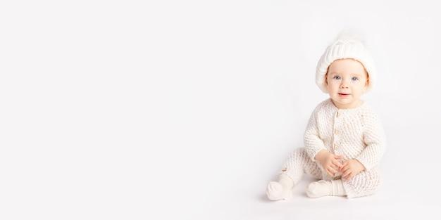 Il bambino striscia in un vestito caldo e un cappello su una priorità bassa isolata bianca
