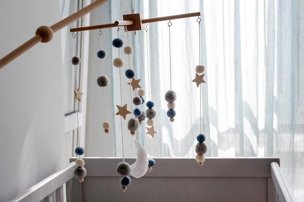 Giostrina per culla con pianeti di stelle e giocattoli fatti a mano con luna sopra la culla del neonato
