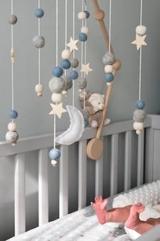 Giostrina per culla con stelle pianeti e luna appesa sopra i giocattoli fatti a mano dei bambini appena nati che dormono sopra...