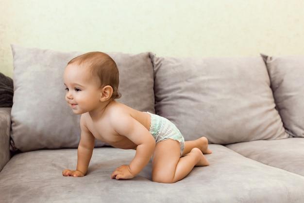 Il bambino in un pannolino striscia sul divano. il bambino ha 11 mesi.