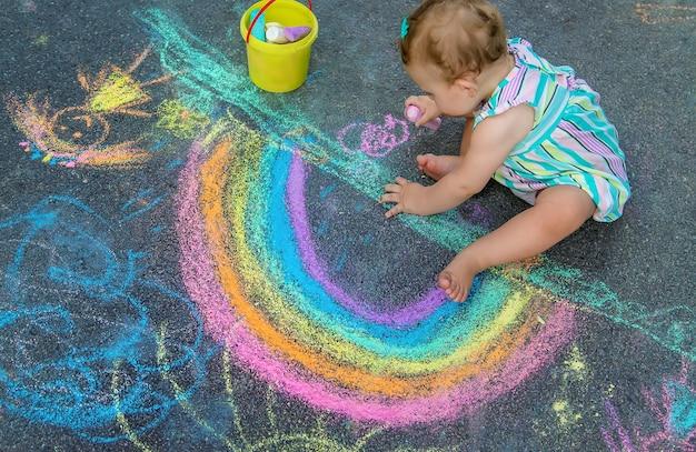 Il bambino disegna un arcobaleno sul marciapiede con il gesso. messa a fuoco selettiva. natura.