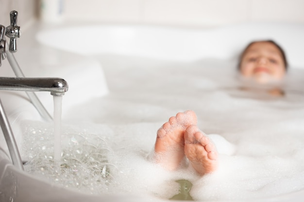 Piedi del bambino in bagno con il primo piano di schiuma e bolle. fare il bagno in una vasca da bagno con schiuma bianca