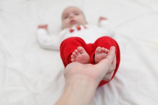 Piedi del bambino nelle mani della mamma.