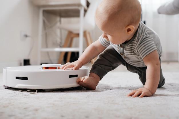 Bambino sul pavimento con robot aspirapolvere. elettrodomestici per famiglie con bambini che semplificano la vita alla mamma. moquette, tappeto riordinatore autonomo, moderno dispositivo per la casa con bambini.