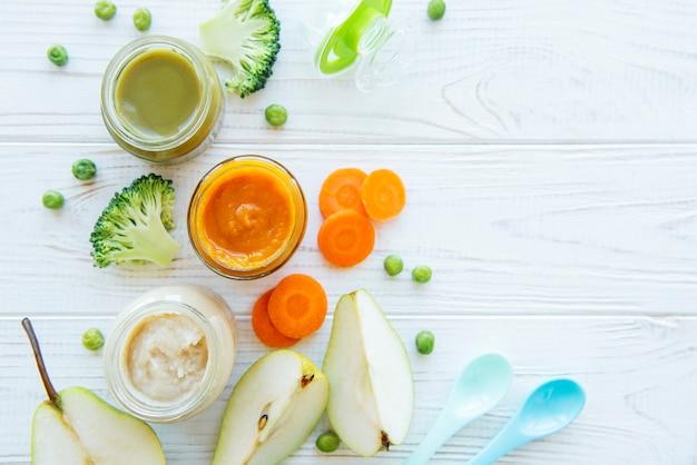 Alimenti per bambini, assortimento di purea di frutta e verdura, piatto, vista dall'alto, spazio per il testo