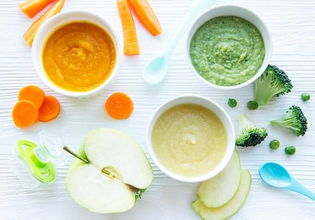 Alimenti per neonati, assortimento di purea di frutta e verdura, piatto lay, vista dall'alto