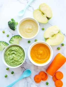 Alimenti per bambini, assortimento di purea di frutta e verdura, piatto, vista dall'alto